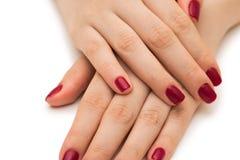 Les mains de femme avec le clou rouge d'isolement sur le blanc Images stock