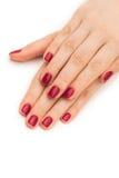 Les mains de femme avec le clou rouge d'isolement sur le blanc Image libre de droits