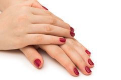 Les mains de femme avec le clou rouge d'isolement sur le blanc Images libres de droits