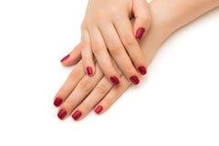Les mains de femme avec le clou rouge d'isolement sur le blanc Photographie stock