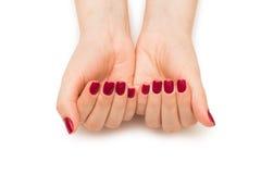 Les mains de femme avec le clou rouge sur le blanc Photo libre de droits