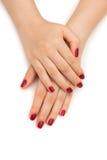Les mains de femme avec le clou rouge sur le blanc Images libres de droits