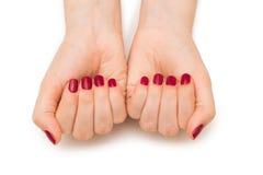 Les mains de femme avec le clou rouge sur le blanc Photographie stock