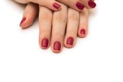 Les mains de femme avec le clou rouge sur le blanc Photos libres de droits