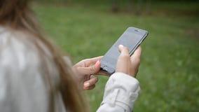 Les mains de femme avec le contact téléphonent des messages de rouleau dactylographiant des doigts de sms banque de vidéos