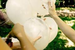Les mains de femme décorant de grands ballons blancs avec des étincelles scintillent photographie stock libre de droits