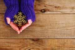 Les mains de femme dans des mitaines tricotées par sarcelle d'hiver légère tiennent le flocon de neige sur le fond en bois Photos libres de droits