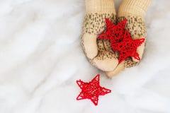Les mains de femme dans des mitaines tricotées par sarcelle d'hiver légère tiennent les étoiles rouges Photos stock