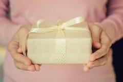 Les mains de femme jugent un boîte-cadeau enveloppé en papier avec le ruban image libre de droits