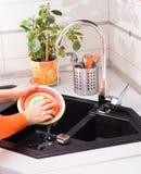 Les mains de femme lavent le plat avec l'éponge dans la cuisine moderne Photographie stock libre de droits