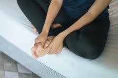 Les mains de femme lui donnant le massage paye dans la chambre à coucher, massage de semelles de pied Photos libres de droits
