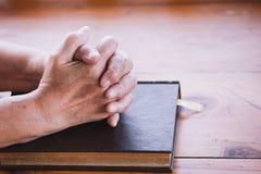 Les mains de femme plus âgée se sont pliées dans la prière sur une Sainte Bible Images libres de droits