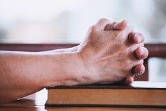 Les mains de femme plus âgée se sont pliées dans la prière sur une Sainte Bible Image stock
