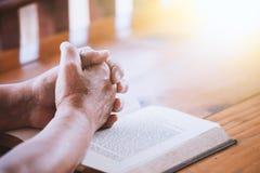 Les mains de femme plus âgée se sont pliées dans la prière sur une Sainte Bible Images stock