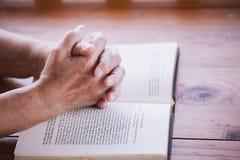Les mains de femme plus âgée se sont pliées dans la prière sur une Sainte Bible Photo libre de droits