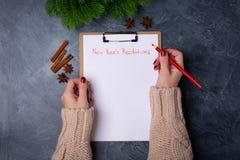 Les mains de femme préparent pour écrire les résolutions de nouvelle année concernant la liste vide sur le fond foncé Configurati image stock