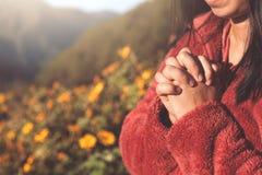 Les mains de femme se sont pliées dans la prière au bel arrière-plan de nature photos libres de droits