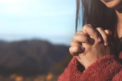 Les mains de femme se sont pliées dans la prière au bel arrière-plan de nature photo stock