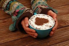 Les mains de femme tiennent la pleine tasse de café de cappuccino de latte Image libre de droits