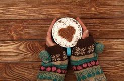 Les mains de femme tiennent la pleine tasse de café de cappuccino de latte Images libres de droits