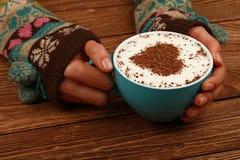 Les mains de femme tiennent la pleine tasse de café de cappuccino de latte Image stock