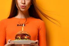 Les mains de femme tiennent le grand sandwich à barbecue d'hamburger avec du boeuf et la bougie allumée pour la fête d'anniversai image libre de droits
