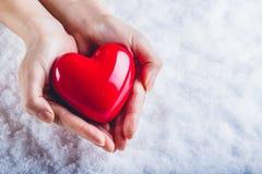 Les mains de femme tiennent un beau coeur rouge brillant à un arrière-plan de neige Concept d'amour et de St Valentine Photographie stock