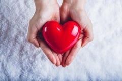 Les mains de femme tiennent un beau coeur rouge brillant à un arrière-plan de neige Concept d'amour et de St Valentine Images stock