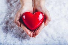 Les mains de femme tiennent un beau coeur rouge brillant à un arrière-plan de neige Concept d'amour et de St Valentine Photo libre de droits
