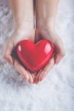 Les mains de femme tiennent un beau coeur rouge brillant à un arrière-plan de neige Concept d'amour et de St Valentine Photographie stock libre de droits