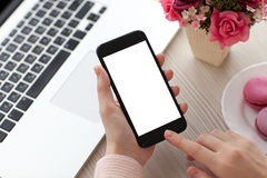 Les mains de femmes tenant le téléphone examinent près de l'ordinateur portable en café Photos libres de droits