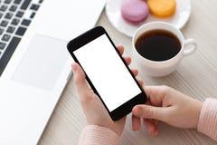 Les mains de femmes tenant le téléphone ont isolé l'écran avec du café et l'ordinateur portable Photo libre de droits