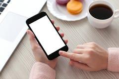 Les mains de femmes tenant le téléphone ont isolé l'écran avec du café et l'ordinateur portable Images stock