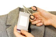 Les mains de fille enlevant la coupe marquent le prix à payer de conseil outre de la laine grise Photos libres de droits