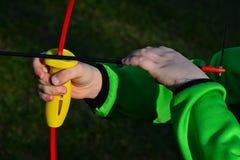 Les mains de garçon ajustant une flèche sur le reste de flèche d'enfants cintrent Images libres de droits