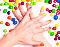 Les mains de jeune femme ont croisé avec la manucure et les sucreries lumineuses autour Image stock