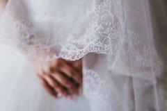 Les mains de jeune mariée sur la robe blanche, préparent pour la cérémonie de mariage, attendant Image stock