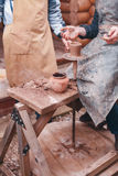 Les mains de l'aide de potier font le broc sur la roue de poterie Images libres de droits