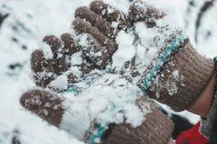 Les mains de l'enfant dans les gants de laine tricotés dans la neige photos libres de droits
