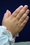 Les mains de l'enfant dans la pose de prière. Photo stock