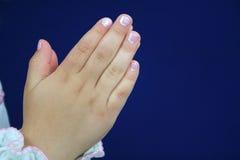 Les mains de l'enfant dans la prière. Photo stock