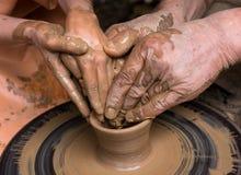 les mains de l'enfant et de l'adulte ont moulé le vesse en céramique Photos stock