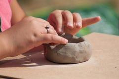 Les mains de l'enfant faisant la poterie d'argile roulent dans extérieur images libres de droits