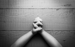 Les mains de l'enfant pliées ensemble dans la prière Images libres de droits