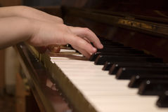 Les mains de l'enfant sur le roulis de piano Photos libres de droits