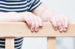 Les mains de l'enfant sur un conseil photos stock
