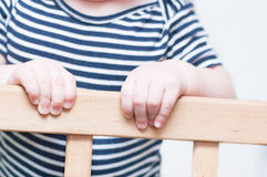 Les mains de l'enfant sur un conseil Images libres de droits