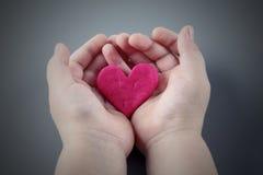 Les mains de l'enfant tenant le coeur rose criqué Photographie stock libre de droits
