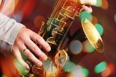 Les mains de l'homme avec le saxophone sur des lumières de bokeh images libres de droits