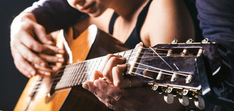 Les mains de l'homme brouillé jouant la guitare acoustique, et la fille de enseignement pour jouer là-dessus Images stock